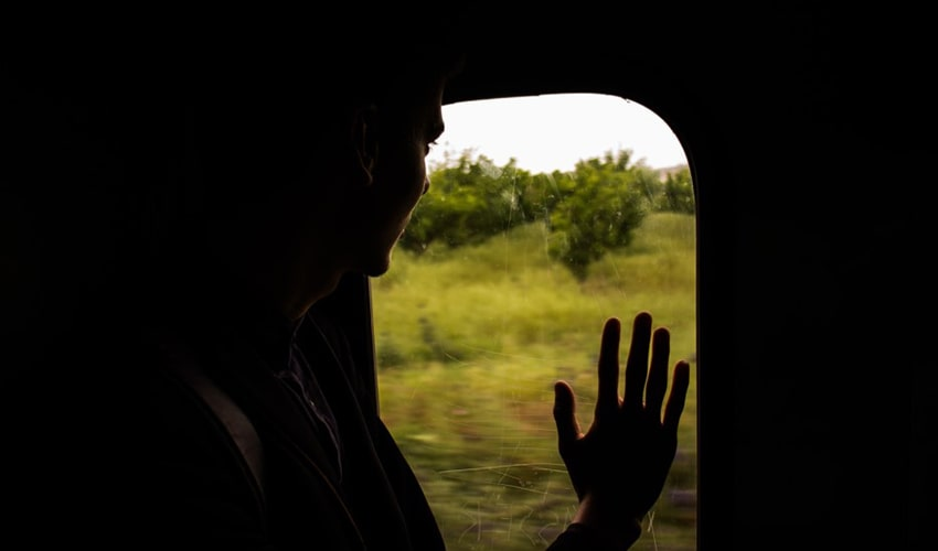 Person looking out of a window of train